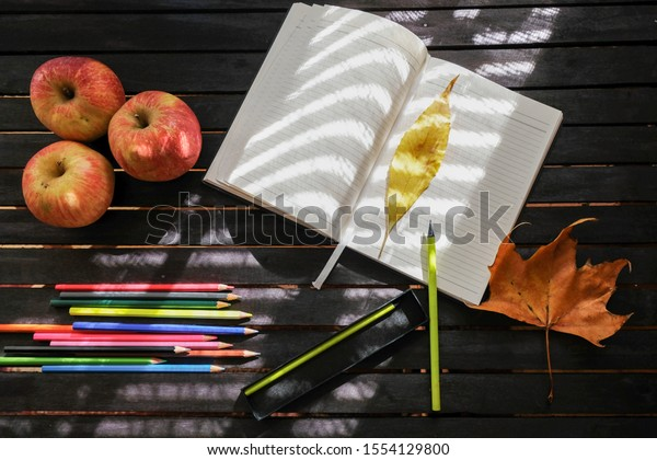 Writers desk in autumn day decorated with apples, pencils, and autumn leaves. Sunshine. Notebook. Colorful background. Wooden table top view.