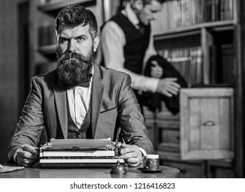 Writers routine concept. Writer working on new book with bookshelves on background. Man with beard and strict face sit in library and work with typewriter, close up. Author types novel or poem.
