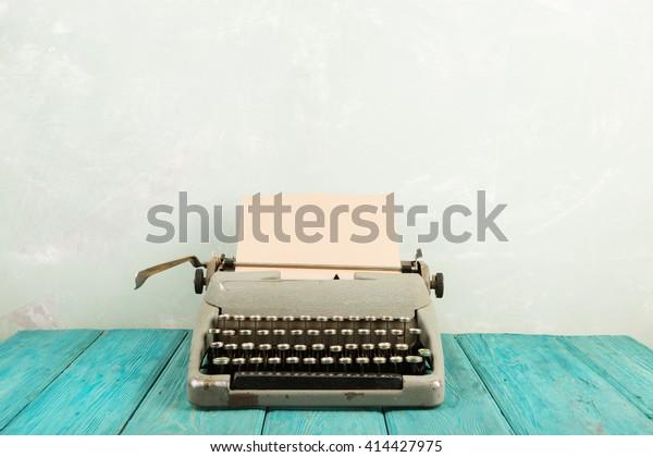 writer's workplace - wooden desk with vintage typewriter