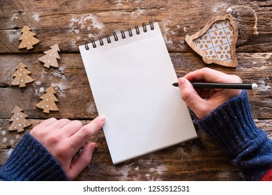 writes Christmas letter on wooden background
