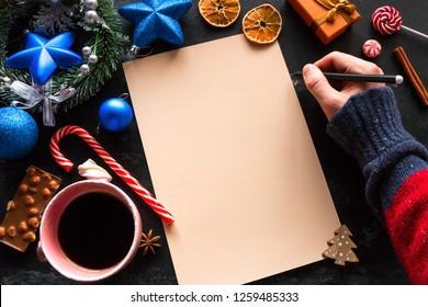 writes christmas wish list on black background