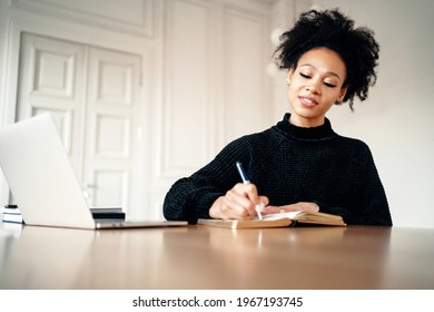 Writes a message to friends sitting on the couch. Typing a message to friends sitting in a chair. Portrait of a woman of Afro appearance using a laptop in her hands. Stylish interior in the apartment.
