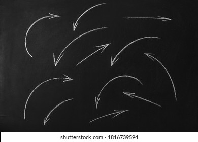 writing arrows with white chalk on blackboard