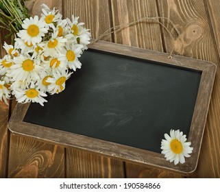 Writing board and daisies on a brown background