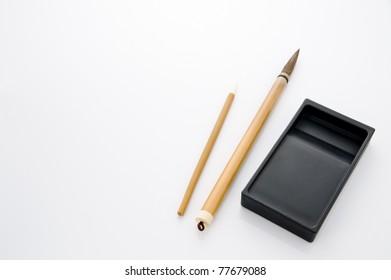 Writing brush and ink stone isolated on white background