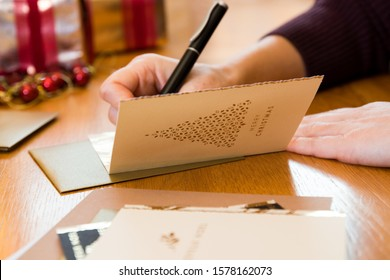 Writing Christmas card with gifts and envelopes on the table