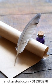 Writing concept. Closeup of scroll and quill near ink-pot on wooden table