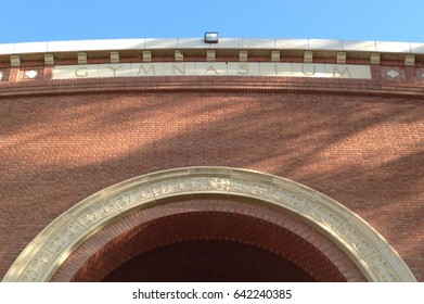 "Writing ""gymnasium"" on a brick facade with an arch"