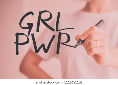 Writing hand. Woman holds pen or marker and writing GRL PWR. Abbreviation for the feminist slogan Girl Power