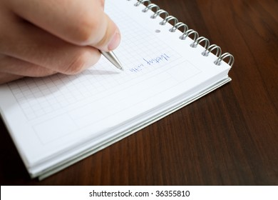 writing meeting message on white notepad closeup