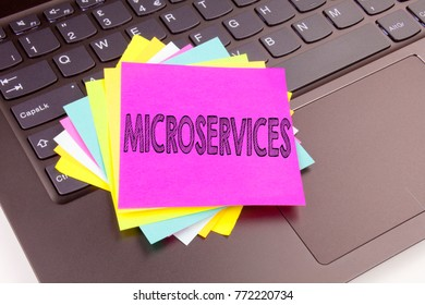 Writing Microservices text made in the office close-up on laptop computer keyboard. Business concept for Micro Services Workshop on the black background with copy space