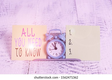 Writing note showing All You Need To Know. Business photo showcasing Tell only the Facts and Important ones Access to Data Mini blue alarm clock standing above buffer wire between two paper.