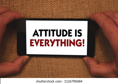 Writing note showing  Attitude Is Everything. Business photo showcasing Personal Outlook Perspective Orientation Behavior Man holding cell phone white screen message app wicker background.