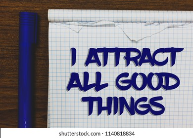 Writing note showing I Attract All Good Things. Business photo showcasing Positive attraction law Motivation Affirmation Written white notepad on grey wooden background beside blue marker.