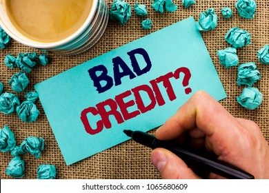 Writing note showing  Bad Credit Question. Business photo showcasing Low Credit Finance Economic Budget Asking Questionaire written by Man Holding Pen on Sticky Note Paper the jute background Cup