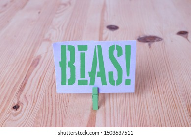 Writing note showing Bias. Business photo showcasing inclination or prejudice for or against one demonstrating group Wooden floor background green clothespin groove slot office.
