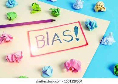 Writing note showing Bias. Business photo showcasing inclination or prejudice for or against one demonstrating group Colored crumpled papers empty reminder blue yellow clothespin.