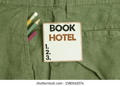 Writing note showing Book Hotel. Business photo showcasing an arrangement you make to have a hotel room or accommodation Writing equipment and blue note paper in pocket of trousers.