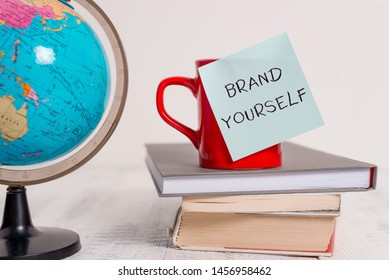 Writing note showing Brand Yourself. Business photo showcasing Develop a unique professional identity Personal product Globe map world earth cup blank sticky note stacked books wooden table.