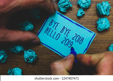 Writing note showing Bye Bye 2018 Hello 2019. Business photo showcasing Starting new year Motivational message 2018 is over Foggy hand hold marker drawn blue notepad paper lump on wooden floor.