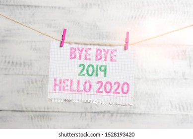 Writing note showing Bye Bye 2019 Hello 2020. Business photo showcasing Starting new year Motivational message 2019 is over Clothesline clothespin rectangle shaped paper reminder white wood desk.