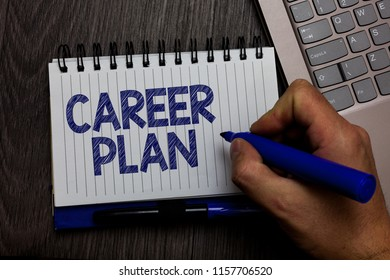 Writing note showing Career Plan. Business photo showcasing ongoing process where you Explore your interests and abilities Man holding marker spiral notebook computer keyboard wooden background.