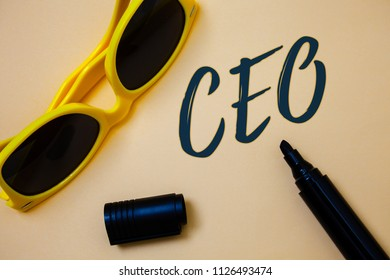 Writing note showing  Ceo. Business photo showcasing Chief Executive Officer Head Boss Chairperson Chairman Controller Ideas messages beige background black marker markers yellow sunglasses.