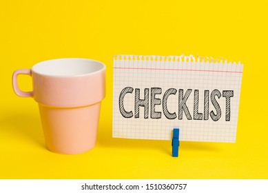 Writing note showing Checklist. Business photo showcasing List down of the detailed activity as guide of doing something Cup empty paper blue clothespin rectangle shaped reminder yellow office.