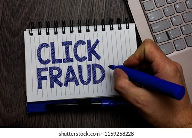 Writing note showing Click Fraud. Business photo showcasing practice of repeatedly clicking on advertisement hosted website Man holding marker spiral notebook computer keyboard wooden background.