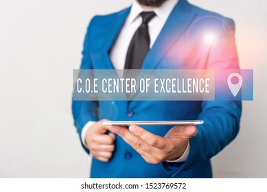 Writing note showing Coe Center Of Excellence. Business photo showcasing being alpha leader in your position Achieve Businessman in blue suite with a tie holds lap top in hands.