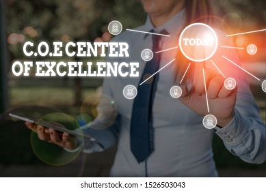 Writing note showing Coe Center Of Excellence. Business photo showcasing being alpha leader in your position Achieve Woman wear formal work suit presenting presentation using smart device.