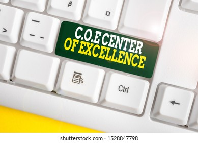 Writing note showing Coe Center Of Excellence. Business photo showcasing being alpha leader in your position Achieve White pc keyboard with note paper above the white background.