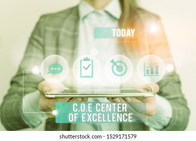 Writing note showing Coe Center Of Excellence. Business photo showcasing being alpha leader in your position Achieve Female human wear formal work suit presenting smart device.
