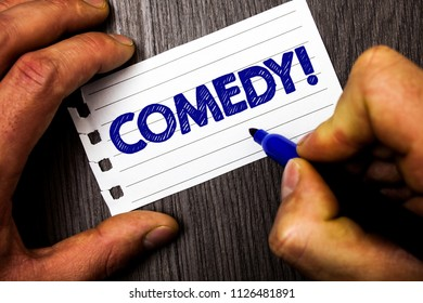 Writing note showing  Comedy Call. Business photo showcasing Fun Humor Satire Sitcom Hilarity Joking Entertainment Laughing Man hold holding marker notebook paper ideas wood wooden background.