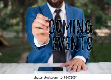 Writing note showing Coming Events. Business photo showcasing Happening soon Forthcoming Planned meet Upcoming In the Future Businessman holds pen and points into copy space.