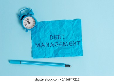 Writing note showing Debt Management. Business photo showcasing The formal agreement between a debtor and a creditor Metal vintage alarm clock crushed sheet marker sky colored background.