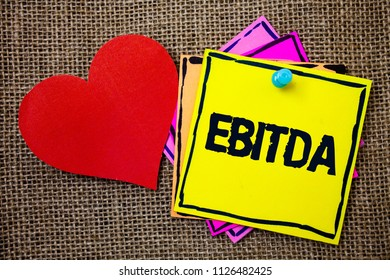 Writing note showing  Ebitda. Business photo showcasing Earnings Before Interest Taxes Depreciation Amortization Abbreviation Ideas messages paper papers red heart love message jute background.