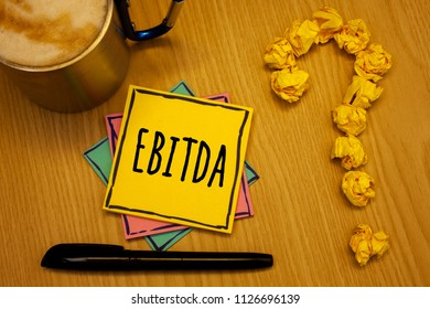 Writing note showing  Ebitda. Business photo showcasing Earnings Before Interest Taxes Depreciation Amortization Abbreviation Message wood table coffee cup question mark crumpled papers.