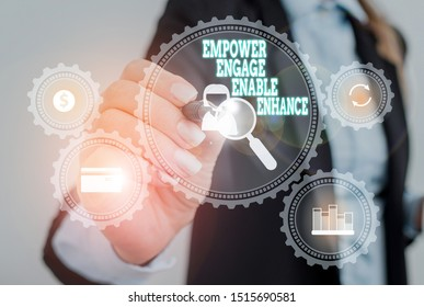 Writing note showing Empower Engage Enable Enhance. Business photo showcasing Empowerment Leadership Motivation Engagement Woman wear formal work suit presenting presentation using smart device.