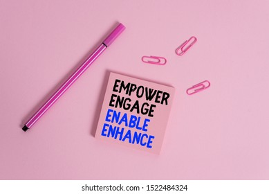 Writing note showing Empower Engage Enable Enhance. Business photo showcasing Empowerment Leadership Motivation Engagement Colored sticky note clips binders gathered pen trendy cool background.