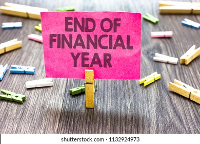 Writing note showing End Of Financial Year. Business photo showcasing Revise and edit accounting sheets from previous year Multiple clips woody table small card clipped notice announcement.