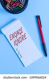 Writing note showing Engage Ignore. Business photo showcasing Silent Treatment Manipulative Punishment Sulking Shunning Notebook and stationary with mouse above pastel backdrop.