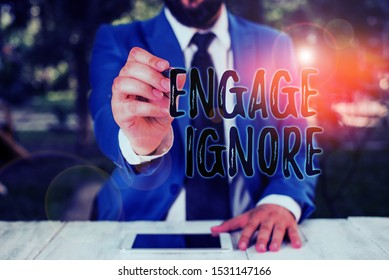 Writing note showing Engage Ignore. Business photo showcasing Silent Treatment Manipulative Punishment Sulking Shunning Businessman holds pen and points into copy space.