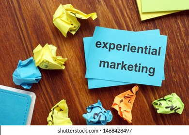 Writing note showing experiential marketing. The text is written on a small colored paper.