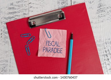 Writing note showing Fiscal Paradise. Business photo showcasing The waste of public money is a great concern topic Colored clipboard crushed sticky note clip marker old wooden background.