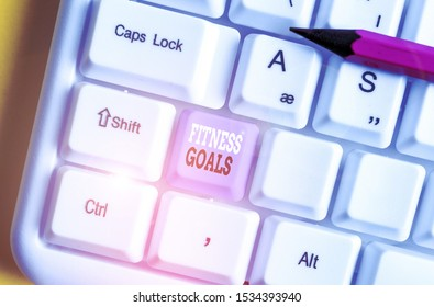 Writing note showing Fitness Goals. Business photo showcasing Loose fat Build muscle Getting stronger Conditioning White pc keyboard with note paper above the white background.