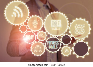Writing note showing Fitness Goals. Business photo showcasing Loose fat Build muscle Getting stronger Conditioning Woman wear formal work suit presenting presentation using smart device.