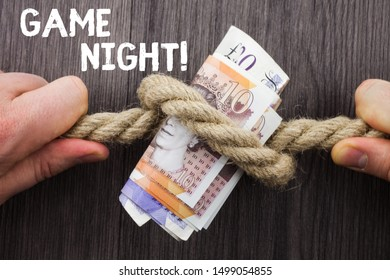 Writing note showing Game Night. Business photo showcasing usually its called on adult play dates like poker with friends Front view wooden background two hands knot rope bills inside symbol.