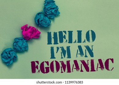 Writing note showing Hello I am An Egomaniac. Business photo showcasing Selfish Egocentric Narcissist Self-centered Ego Drawn blue and red words teal color paper lump mid pink on blue floor.