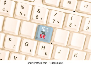 Writing note showing Hello I Am New. Business photo showcasing used greeting or begin telephone conversation White pc keyboard with note paper above the white background.